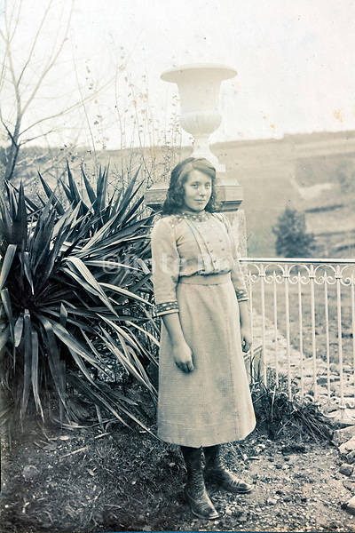 woman standing by Fence of garden France 1900s