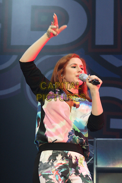 Katy B (Kathleen Anne Brien)<br /> Girlguiding Big Gig 2013 at the Wembley Arena, London, England.<br /> October 12th 2013<br /> on stage in concert live gig performance performing music half length black pink blue white print top singing hand arm in air <br /> CAP/ROS<br /> &copy;Steve Ross/Capital Pictures