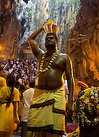man in with  Shivas fork-shaped spear thrilled through his cheeks while Thaipusam ceremonies inside Batu Caves, Kuala Lumpur, Malaysia, 2012. Thaipusam ceremonies, celebrated by tamile Hindu community in Malaysia, take place  in Sanctuary of Batu Caves at the border of Kuala Lumpur, each year around end of January or beginning of February, according to Hindu moon calendar. The event is paying hommage to Lord Murugan, a spirit or god created by Shiva to lead the army of gods against the army of evil demons, finally defeating the evil spirits. There are many ways to present offerings or sacrifices for this major religious event. Devotees mortify their bodies by carrying heavy kavaris with spears fixed in their skin or fruits, flowers and little post with holy milk fixed with hooks in their skin, ascending the stairways to the sanctuary in trance, `followed by assistant  taking care and musicians playing loud and fast rhythmic trance music.  Many families shave their head in a ritual before ascending the stairways, as part of rituals to obtain salvation for their ancestors.