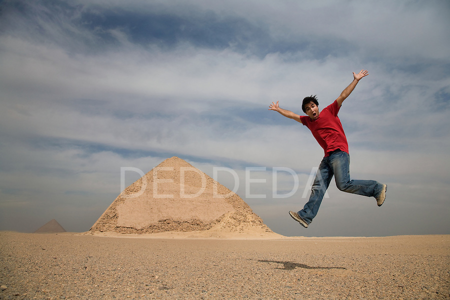 A male toursit jumps into the air at the Bent Pyramid, located 10km south of Saqqara in Dahshur, Egypt.