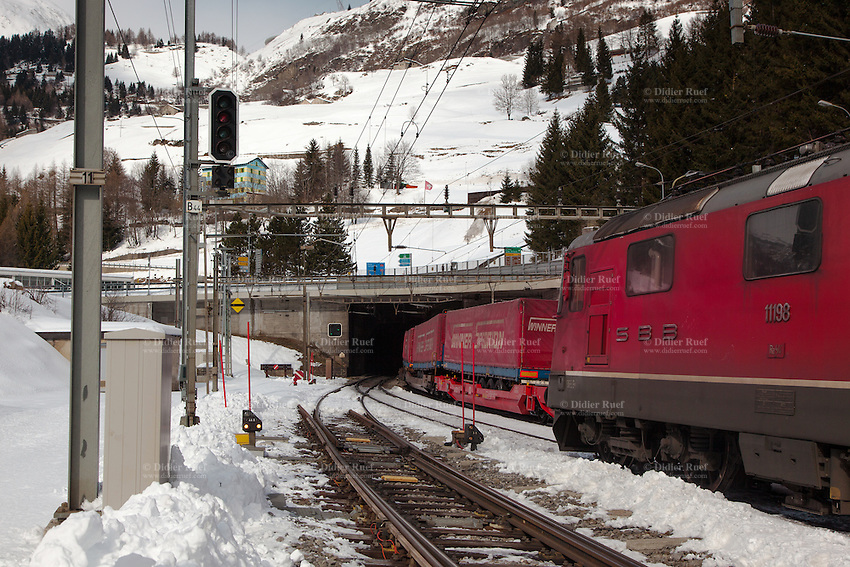 Switzerland. Canton Ticino. Airolo. Alps and Leventina valley. Swiss flag. Two SBB CCF FFS freight trains at the Gotthard Rail Tunnel. One goes in, the other comes out. North-south traffic by rail. Locomotive. The Gotthard Tunnel (German: Gotthardtunnel, Italian: Galleria del San Gottardo) is a 15.003 km (9.322 mi) long railway tunnel and forms the summit of the Gotthard Railway in Switzerland. It connects Göschenen with Airolo and was the first tunnel through the Gotthard massif. It is built as one double-track, standard gauge tunnel. The trip takes about seven to eight minutes by train. Services are operated by the Swiss Federal Railways. 8.03.2016  © 2016 Didier Ruef