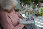 Model released senior adult woman sitting doing a crossword puzzle, UK