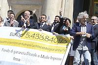 Roma, 20 Maggio 2014<br /> Il Movimento 5 stelle ha presentato in Piazza Montecitorio davanti la Camera dei Deputati, un assegno da 5 milioni 433 mila e 840 euro con la metà delle indennità dei parlamentari insieme alle eccedenze della diaria non rendicontata. Presente anche il leader Beppe Grillo.<br /> I soldi vanno al Fondo di garanzia per piccole e medie imprese.