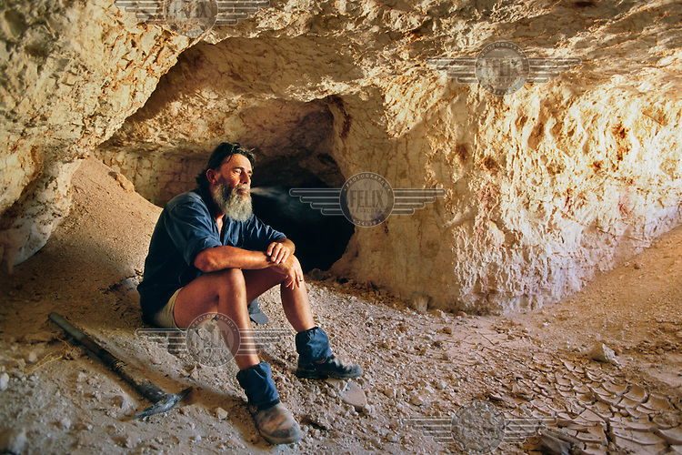 Australian miner Andrew Girvan smokes a cigarette at the entrance to an opal mine.  He does not have the necessary machinery to mine underground so intead specialises in noodling, searching for remaining opal among disused mine shafts...