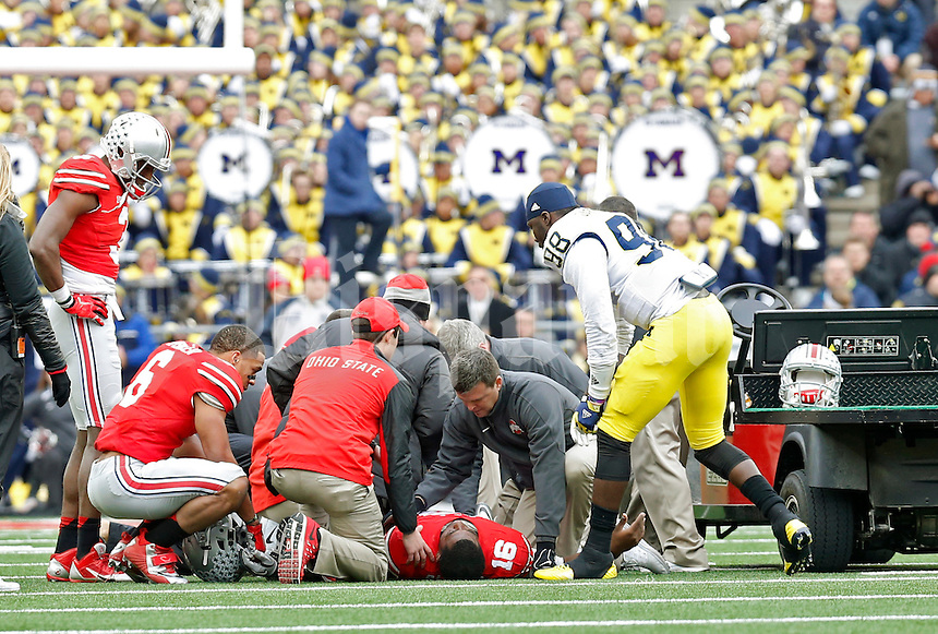 Michigan Wolverines quarterback Devin Gardner (98) checks on Ohio State Buckeyes quarterback J.T. Barrett (16) after getting hurt in the 4th quarter of their game at Ohio Stadium in Columbus, Ohio on November 29, 2014.  (Dispatch photo by Kyle Robertson)