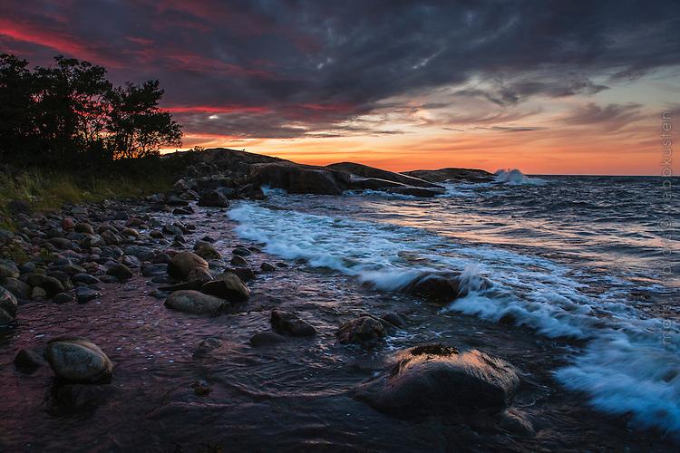 Kulingvågor mot klippor i skymningen på Norra Arholma i Stockholms norra skärgård Roslagen