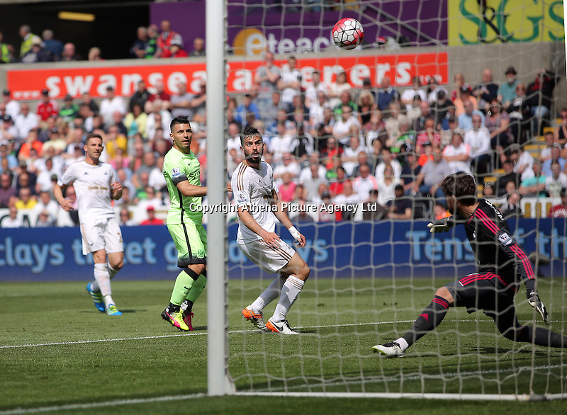 Kristoffer Nordfeldt of Swansea City (R) saves the ball from a kick by Sergio Aguero of Manchester City (L) during the Swansea City FC v Manchester City Premier League game at the Liberty Stadium, Swansea, Wales, UK, Sunday 15 May 2016