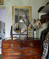 On an antique chest-of-drawers in the dressing room a old fashioned swivel mirror and table lamp in front of a gilt-framed print of Louis XIV
