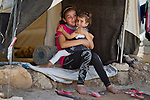 A young female Syrian refugee holds a family member in the entrance of their tent inside the Domiz refugee camp in Iraqi-Kurdistan. The camp, run by the UNHCR and International Rescue Committee, is home to around 4,500 refugees who have fled from the ongoing Syrian civil war with up to 400 new inhabitants arriving every day.  Built on the site of a former Iraqi Army base that was bombed during the 2003 Coalition forces invasion of Iraq, the camp was cleared of cluster bombs and unexploded ordnance by the Mines Advisory Group (MAG), a demining NGO working in Iraqi-Kurdistan.
