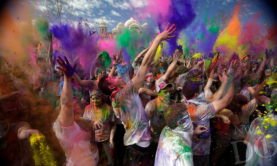 Revelers throw colored corn starch into the air as they celebrate the 2015 Holi (Festival of Colors) at the Krishna Temple in Spanish Fork, Utah on Saturday, March 28, 2015. (AP Photo/Rick Bowmer)