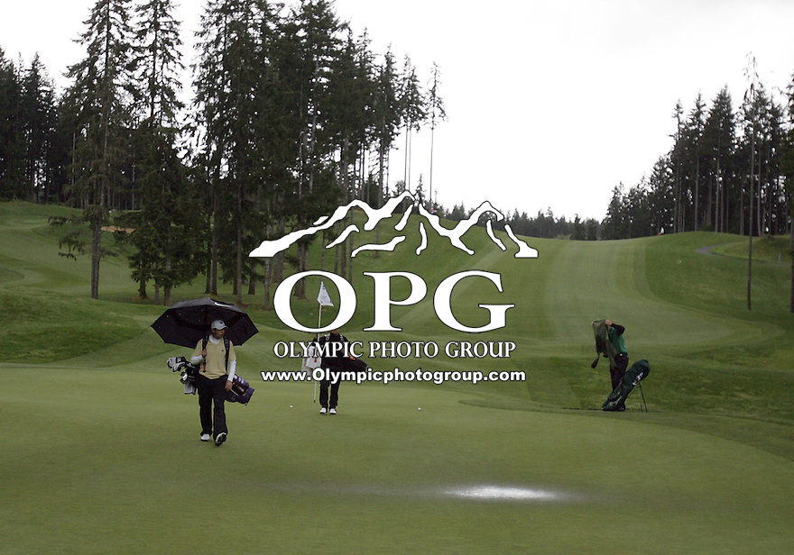 Washington's Darren Wallace (left), Diego Velasque of Oregon State (center) and Dustin Morris of Colorado State (right) walk off the wet playing service of hole 6 during the first round of the NCAA West Regionals.