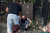 Moscow, Russia, 25/07/2010..A drunk man falls into a grave as hundreds of Russians gather at the grave of legendary bard singer, poet and actor Vladimir Vysotsky to mark the 30th anniversary of his death. Vysotsky, an alcoholic and heroin addict who died in 1980 aged 42 of a heart attack, is best known for his songs of Soviet prison and military life, and his acting on stage and screen. Much of his work was officially unpublished during his lifetime, and he remains a potent anti-authoritarian symbol of protest to Russians of all ages even today.
