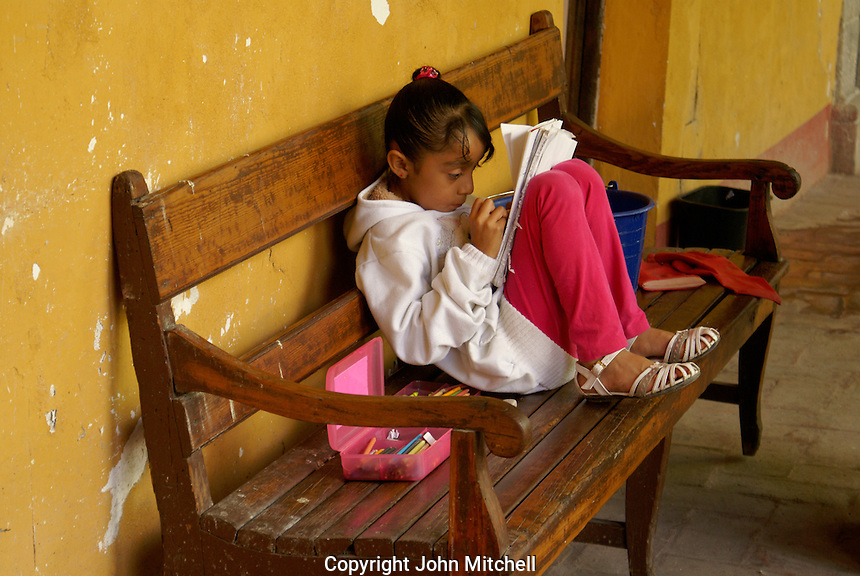 Young girl reading and coloring in San Miguel de Allende, Mexico. San Miguel de Allende is a UNESCO World Heritage Site....