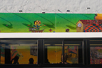 Passengers on a bus watch Os Gemeos completing a new Mural on the site of the old Keith Haring Mural