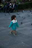 Arequipa, Peru. Peruvian child (girl, Peruvian) walking in public park; pigeons in background. No MR. ID: AL-peru.
