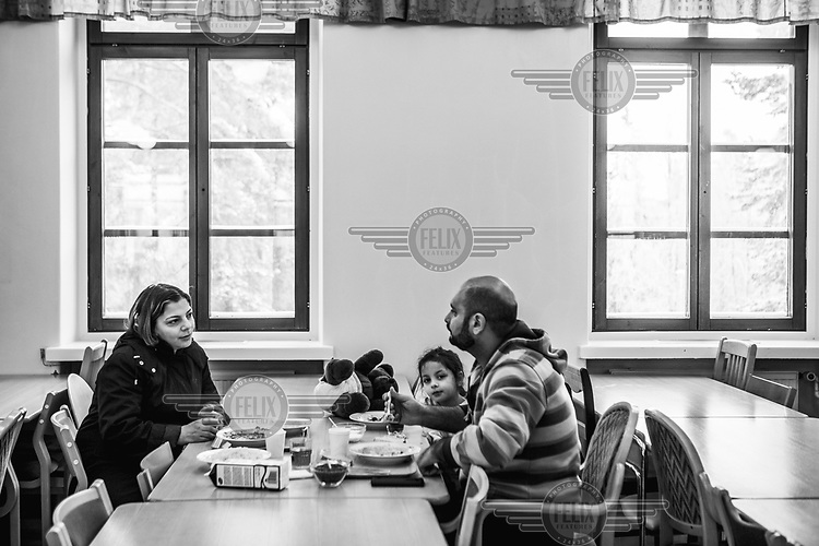 A family eating in the refectory at the Tarina refugee shelter..