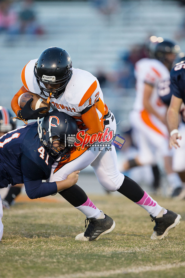 Deshawn Howie (12) of the Northwest Cabarrus Trojans is tackled by Isaac Bell (41) of the Carson Cougars in JV football action at Jesse Carson High School on October 24, 2014, in China Grove, North Carolina.  The Cougars defeated the Trojans 35-6.  (Brian Westerholt/Sports On Film)