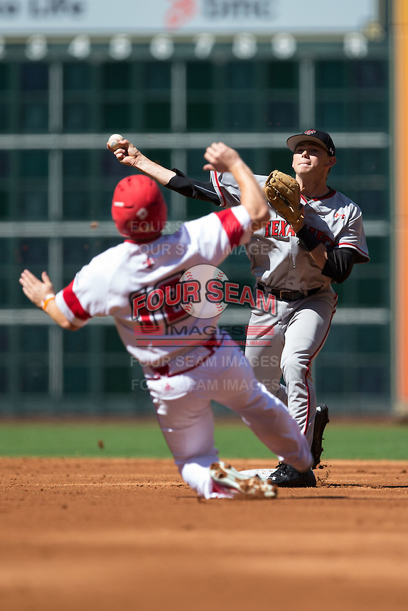 Michael Davis (3) of the Texas Tech Red Raiders turns a double play as Joe Robbins (12) of the Louisiana-Lafayette Ragin' Cajuns slides into second base at Minute Maid Park on February 27, 2016 in Houston, Texas.  The Red Raiders defeated the Rajin' Cajuns 5-3 in 10 innings in game four of the 2016 Shriners Hospitals for Children College Classic.  (Brian Westerholt/Four Seam Images)