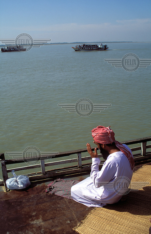 © Neil Cooper / Panos Pictures..Sandwip Isles, BANGLADESH..Muslim man praying on a ferry.