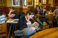 A mother breastfeeding her baby at the table in a pub restaurant.