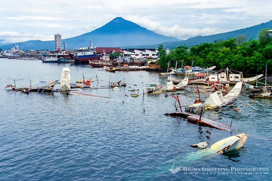 North Sulawesi, Bitung. In the background Gunung Klabat, 2022 m. Sunken illegal fishing vessels, in this case probably confiscated from Philippine fishermen.