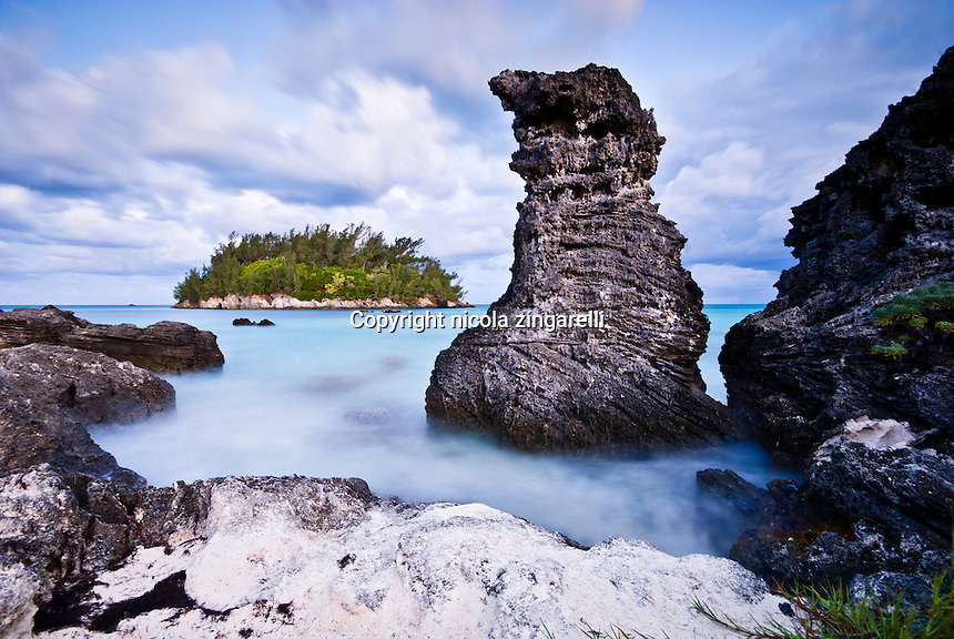 Lava designed rock along the western coast of Bermuda in the Atlantic ocean. A dolmen looking rock surges from the silky waters
