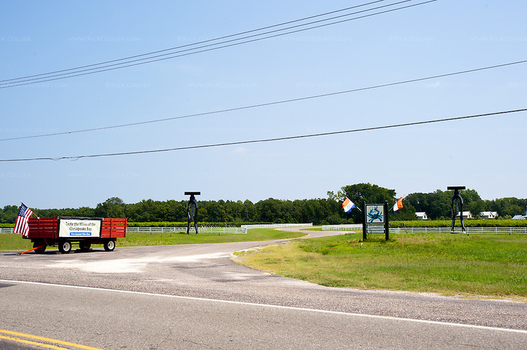 A large wagon stands at roadside, in the center of the driveway entering White Fences Vineyard and Winery.