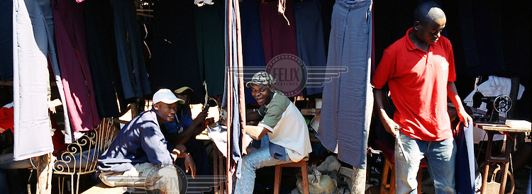 Young men working as clothing tailors at Hulene Market.
