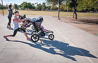Devon Schmidt, with her daughter Morgan, 2, Phx, Near camera, and Sharon Fisher, with Sasha, 22 months, Scottsdale lunge across the basketball court at Desert Horizon Park in Phoenix during their Fit4Mom class. he class uses portable equipment strollers and park landscape to help moms fit a workout into their busy schedules.