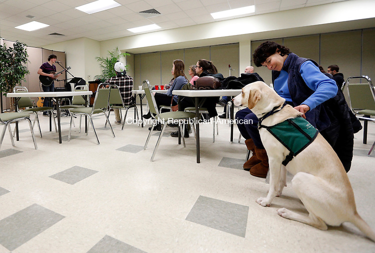 Southbury, CT- 05 February 2015-020515CM05-  Terri-Gayle Mazur and a Maggie a Lab Greyhound mix therapy dog of Souhthbury listen in as Artagnan Mayes, a sophomore at Pomperaug High School puts on a concert for folks at the Souhtbury Community Building in Southbury on Thursday.  Mayes is a member of Chorale and Chamber Choir at the high school.  Mayes performed contemporary songs, along with original ones.  Christopher Massa Republican-American