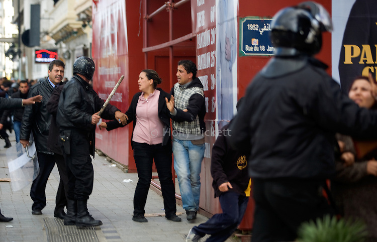 Demonstrators try to get away from the Interior Ministry after a police threw tear gas at a protest in downtown Tunis, Tunisia, Jan. 14, 2011. Several thousand people gathered outside the Ministry to protest and ask President Zine El Abidine Ben Ali to resign.