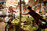 VIETNAM, Hanoi, a woman and son on their moped buy vegetables in the Chau Long Market