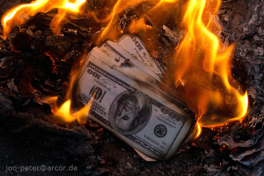 symbolic dollar bills are burned for spirits and ancestors in a spiritual world, city Hanoi, Vietnam.  Vietnamese belief is a blend of Buddhism, Taoism and animism.