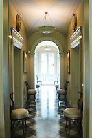 The corridor is lined with a set of matching chairs and is suffused with light from French windows at the far end
