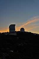 McDonald Observatory at sunset as the clouds light up with these colorful pinks and oranges over the tops of the two observatory in the skies over the Davis MountainsThe dark skies in this area is why the McDonald Observatory is located here. These telecopes are sitting on top of this Mount Locke the two domes seen are the Otto Struve and the Harlan J. Smith in view.
