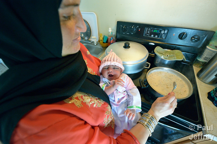 Parwana Ahmadzai holds her one-week old infant daughter Afsana as she cooks in her home in Harrisonburg, Virginia. Ahmadzai and her family, refugees from Afghanistan, were resettled in Harrisonburg by Church World Service.<br /> <br /> Photo by Paul Jeffrey for Church World Service.