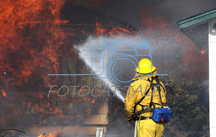 A Reno firefighter tries to save an outbuilding as a house burns in a 400-acre brush fire in south Reno, Nev., on Friday, Nov. 18, 2011. More than 25 homes have been lost as high winds with gusts up to 60 mph drive the flames.  (AP Photo/Cathleen Allison)