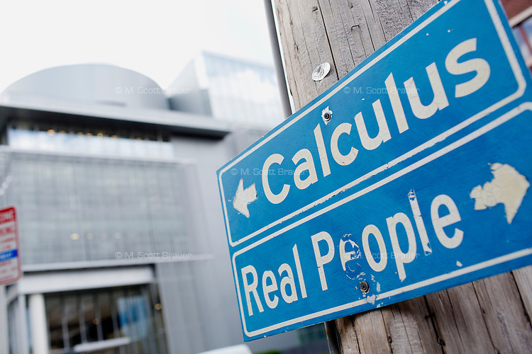 """A sign near MIT's Media Lab points toward the building saying """"Calculus"""" and reads """"Real People"""" pointing toward MIT buildings housing the Sloan School of Management and the Department of Political Science at MIT in Cambridge, Massachusetts, USA."""