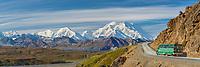 Tour bus travels the Eielson bluffs on the Denali park road, with Denali visible along the Alaska Range horizon.