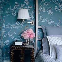 A close-up of a bamboo-framed bedside cabinet and a wall covered in Earlham hand-painted wallpaper by De Gournay
