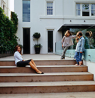 Emma Roig and her three children on the steps leading up to their London home