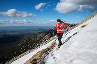 Two Female hiker crosses snow near summit of Koscielec (2155m), Tatra mountains, Poland