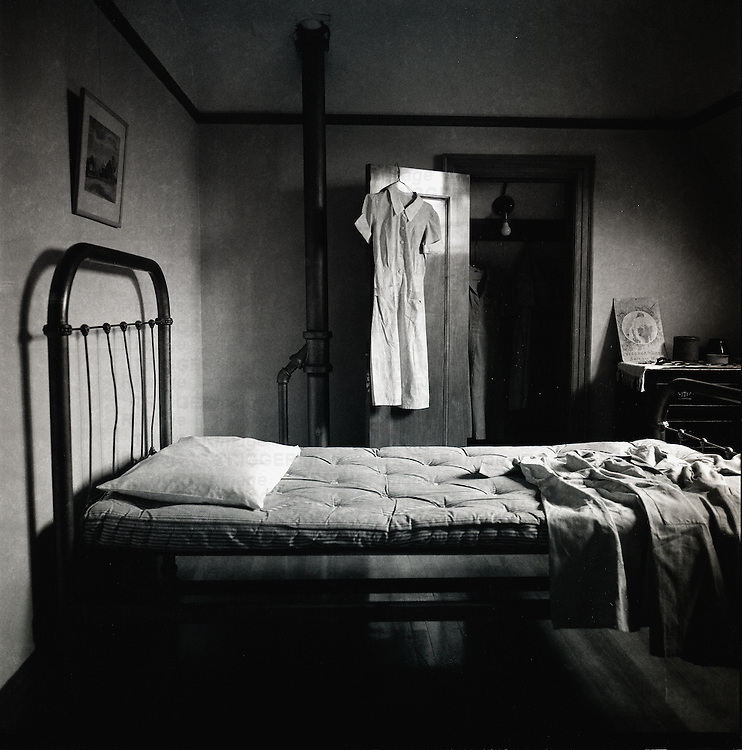 An old fashioned bedroom with mattress on bed and open wardrobe