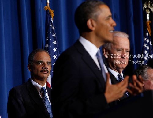 United States Attorney General Eric Holder listens as U.S. President Barack Obama makes remarks at the Department of Interior in Washington, D.C. before signing the Violence against Women Act on March  7, 2013. .Credit: Dennis Brack / Pool via CNP