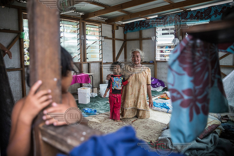 Galilee Naichaus, 62, with her granddaughters Penvangali (four) and Mesepa (six, left) inside their house that was damaged by Cyclone Pam. Nui Island, Tuvalu.<br /> Galilee says: 'Two of my houses were broken by waves, this one survived, but plenty of water came inside. We took shelter in our relative's home on the other side of Nui. When we went back all things were wet, but we are happy to still have our house, other families lost everything.'
