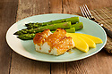 Grilled glazed white fish served with asparagus and mango slices