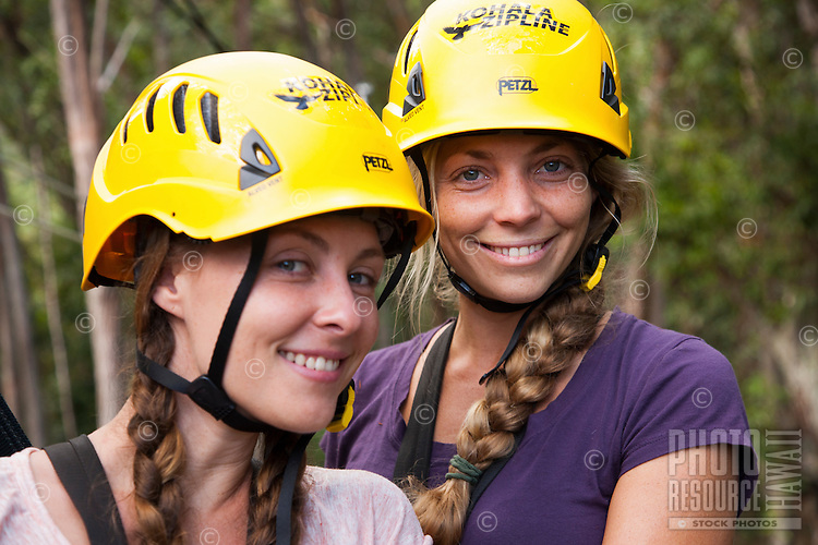 Portrait of two sisters wearing safety helmets while Ziplining on the Big island with Kohala zipline
