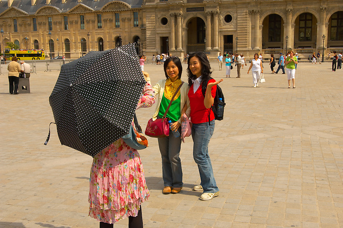 Oriental girl tourists having their photo taken at the Louvre Paris