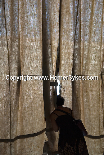 Woman looking through curtain Italy