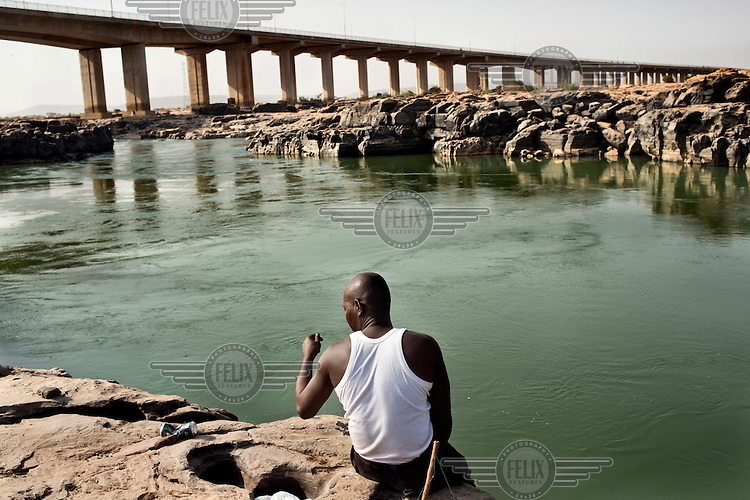 A man fishing on the banks of the River Niger with a Chinese built bridge spanning the river in the background. The bridge was opened in September 2011 and is the third crossing of the Niger in Bamako.